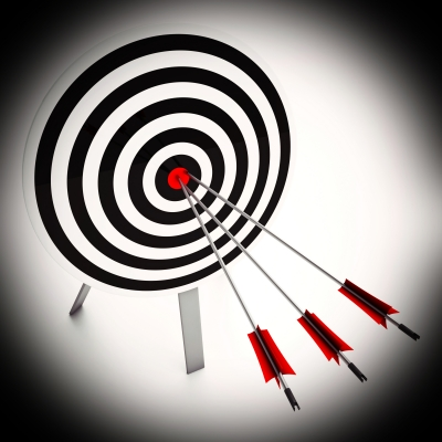 Three red-fletched arrows protrude from a black and white ringed archery target, all three points are in the red bullseye.